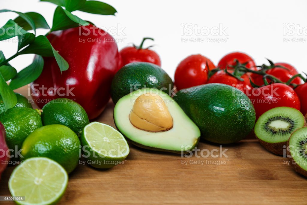 A selection of juicy fruits and vegetables on a wooden and white background. stock photo