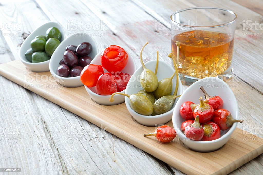 Selection of olives and peppers with whiskey stock photo