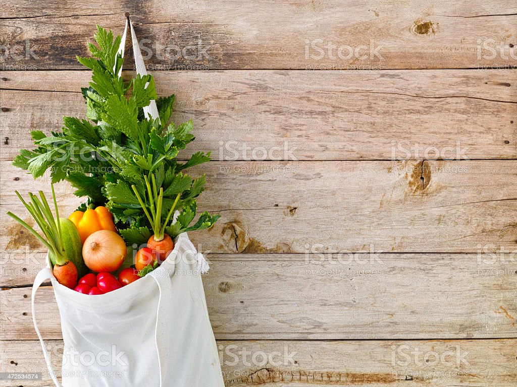 Selection of salad vegetables in a cotton bag. stock photo