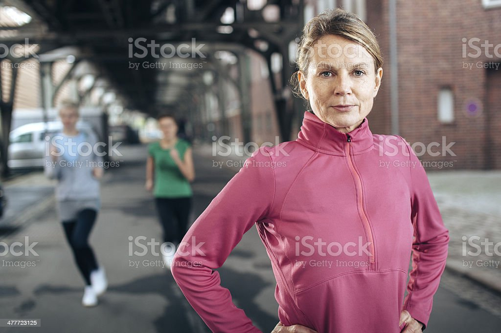 Selective focus image of a mature woman running in a city stock photo