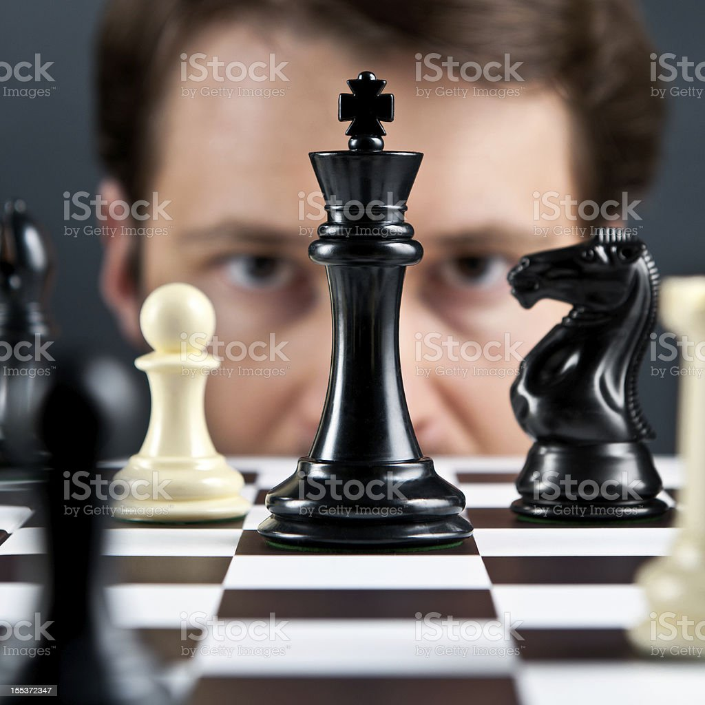 Selective focus, man's eyes on chess pieces stock photo