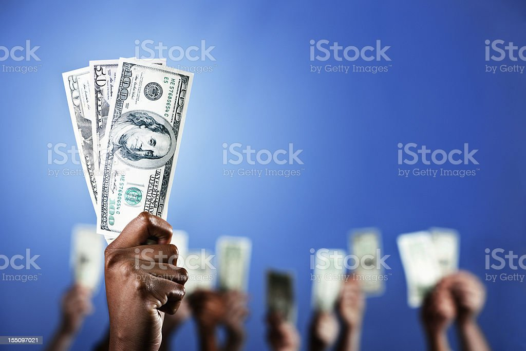 Selective focus, many fists holding up money stock photo