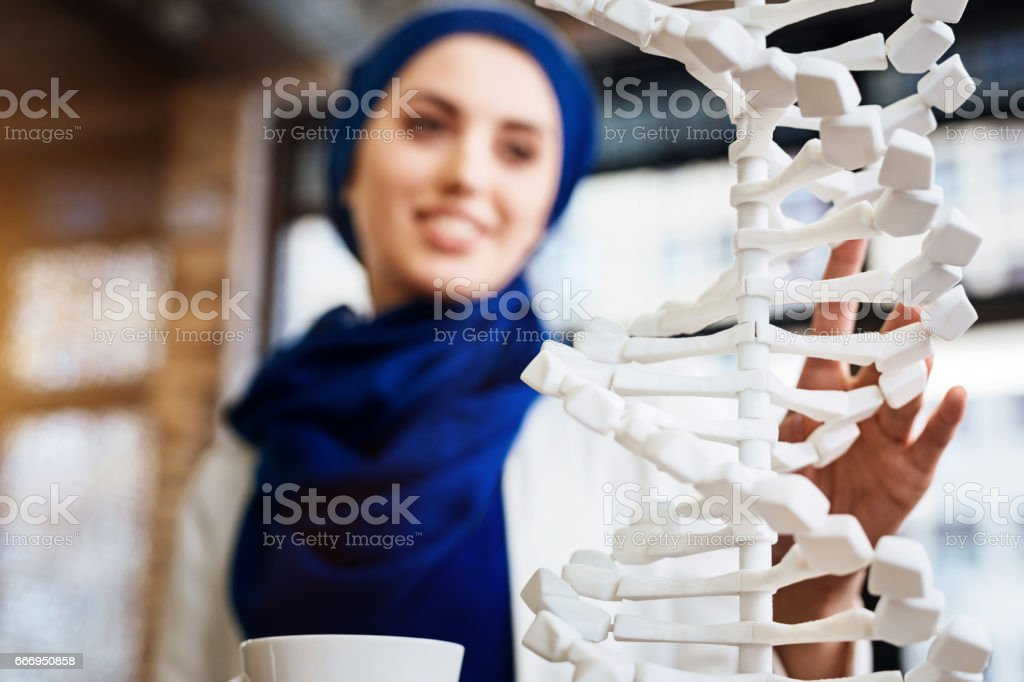 Selective focus of DNA model in hands of muslim student stock photo