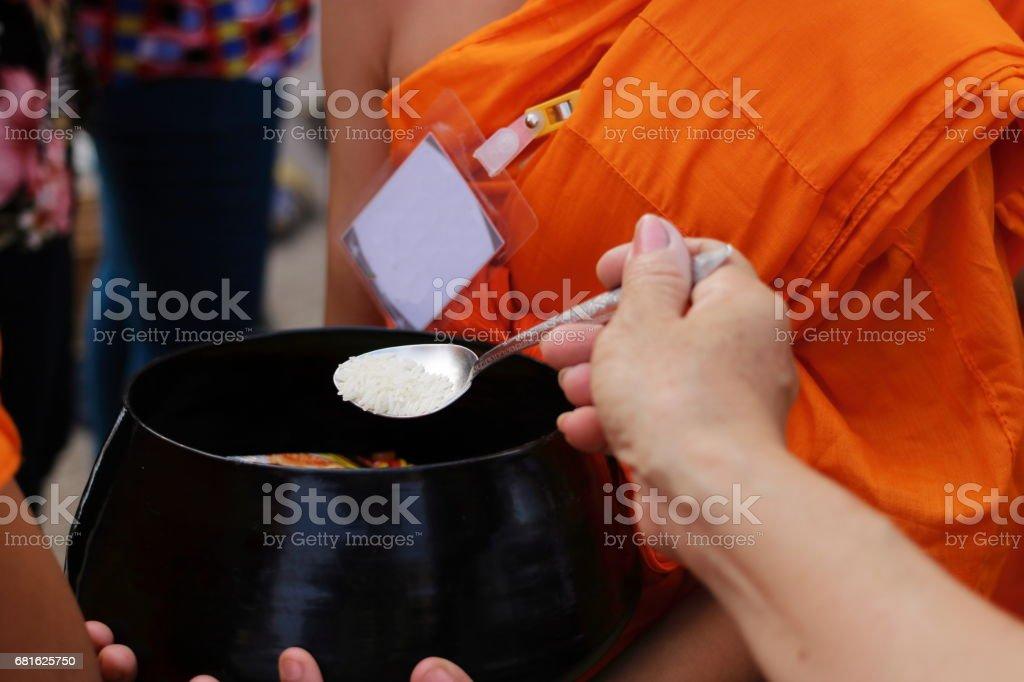 Selective focus on spoon of people while put food to a Buddhist monk's alms bowl in Visakha Puja Day stock photo