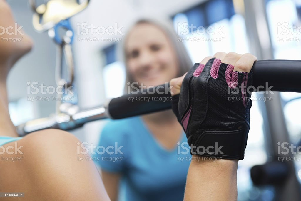 Selective focus; woman using exercise equipment in gym with trainer royalty-free stock photo