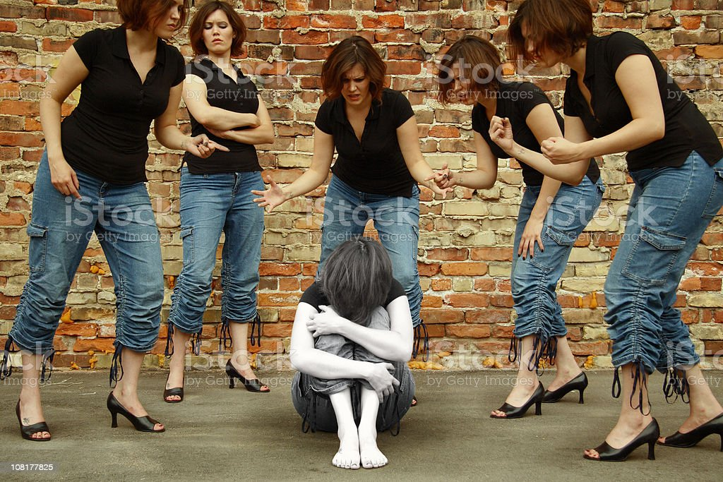 Self- Bullied Woman Cowers Amongst Dopplegangers stock photo