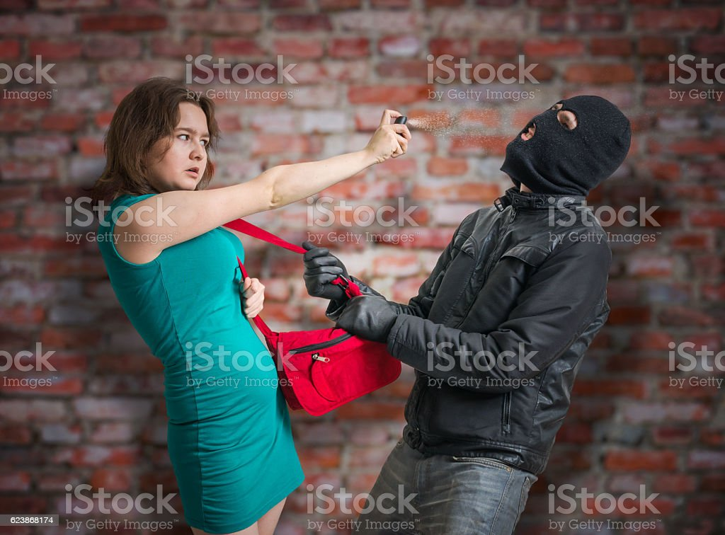Self defense concept. Woman fighting with thief using pepper spray. stock photo