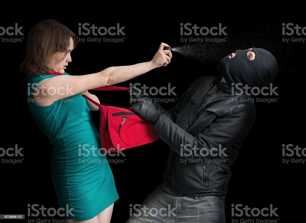 Self defense concept. Young couple is defending with pepper spray. stock photo