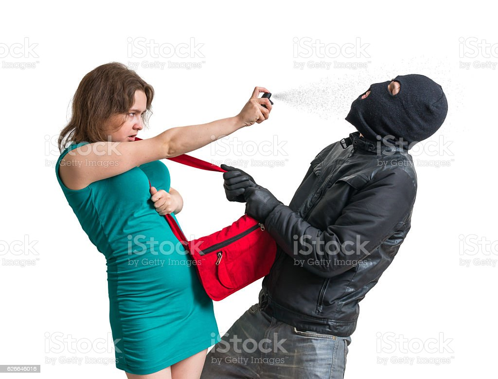 Self defense concept. Young woman is defending with pepper spray. stock photo