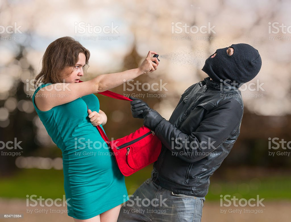 Self defense concept. Young woman is spraying with pepper spray. stock photo