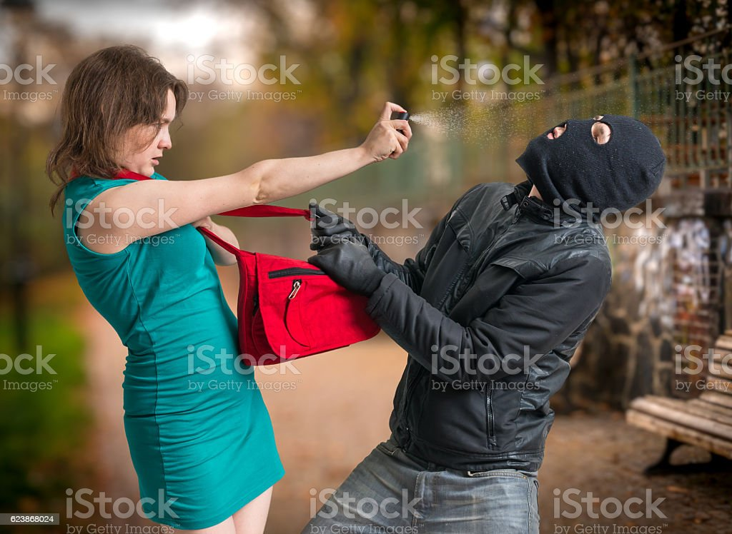 Self defense concept. Young woman is using pepper spray. stock photo