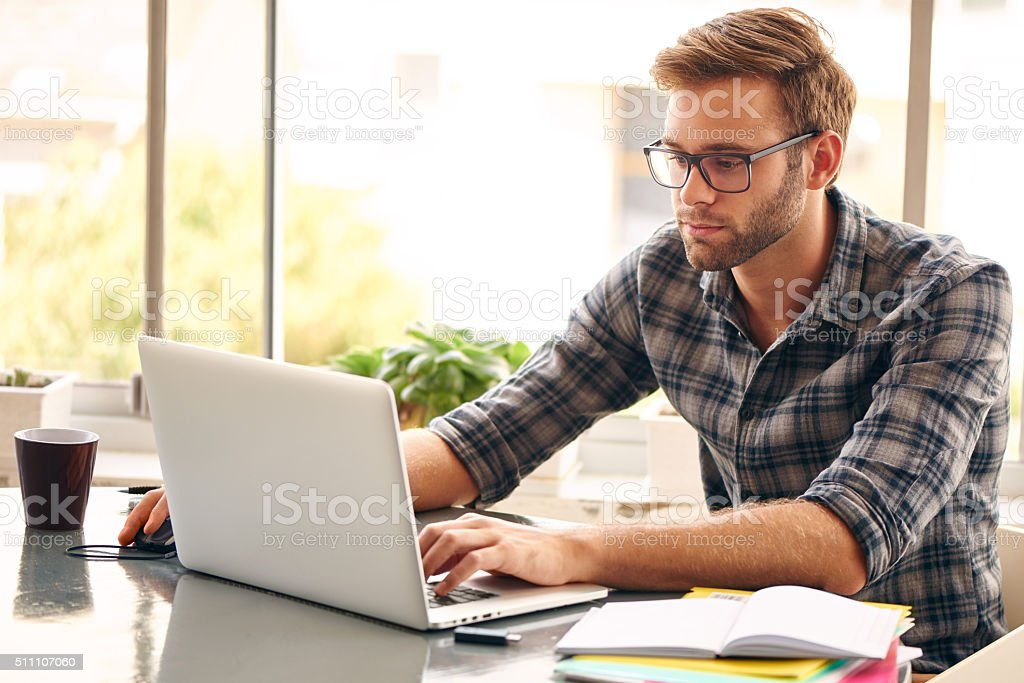 Young man with glasses working on his notebook, with a fresh cup of...