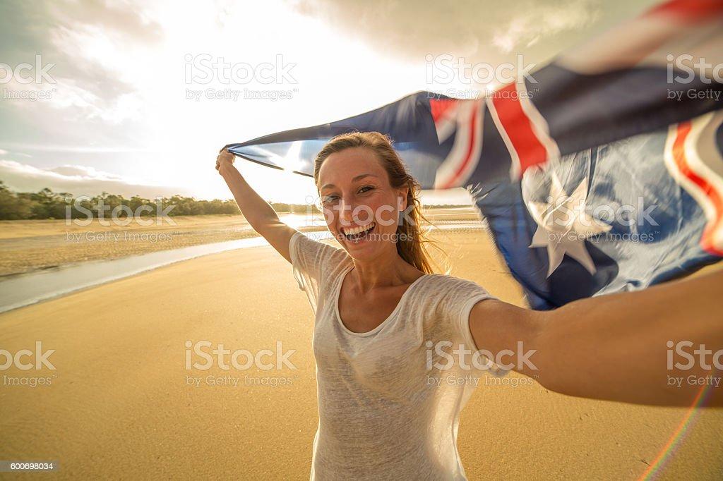 Self portrait of caucasian female holding Australian flag on beach stock photo