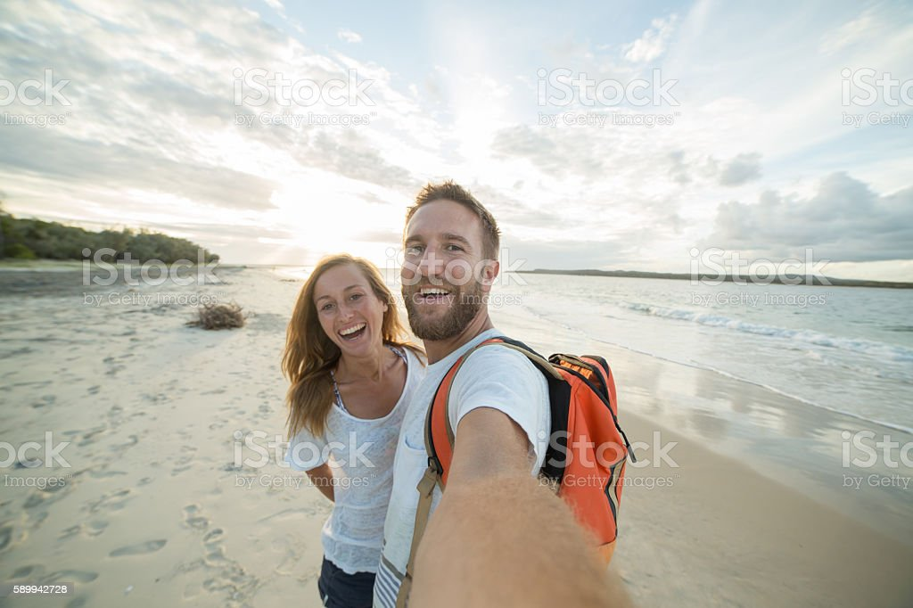 Self portrait of playful young couple on beach at sunset stock photo