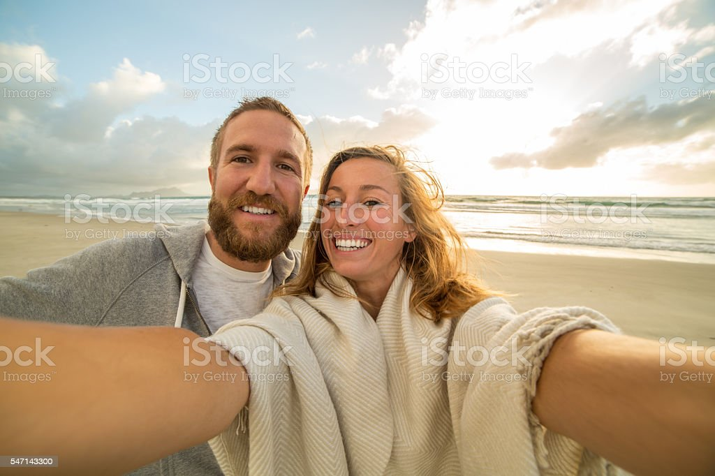 Self portrait of young couple on beach at sunset stock photo