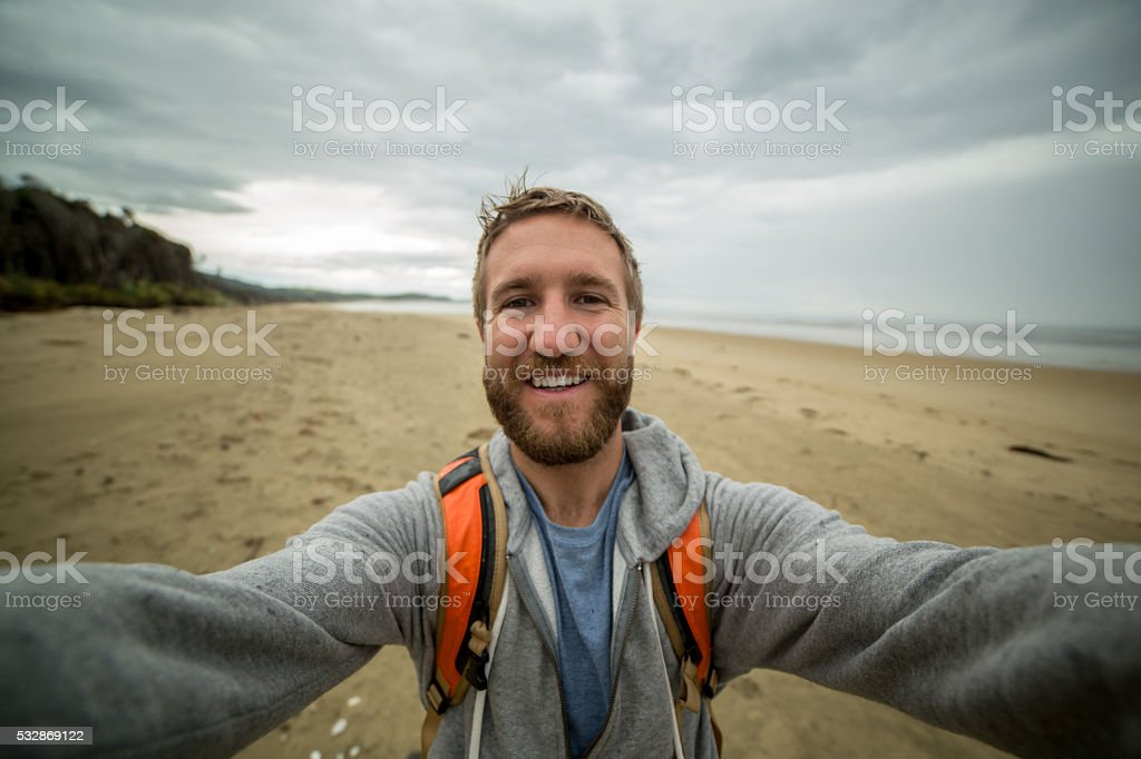 Cheerful young man takes a selfie portrait on a beach. He is wearing...