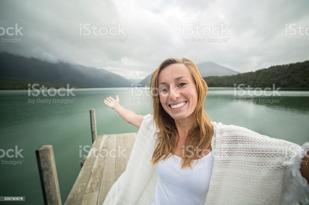 Self portrait of young woman standing on lake pier stock photo