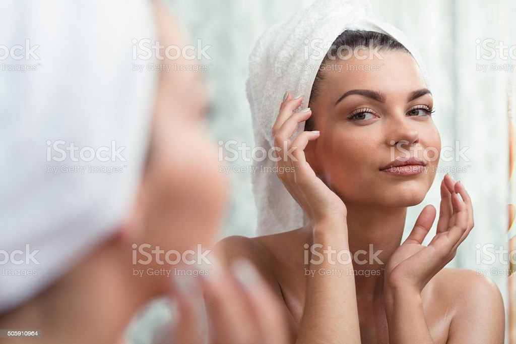 Self-confident brunette looking at reflection stock photo