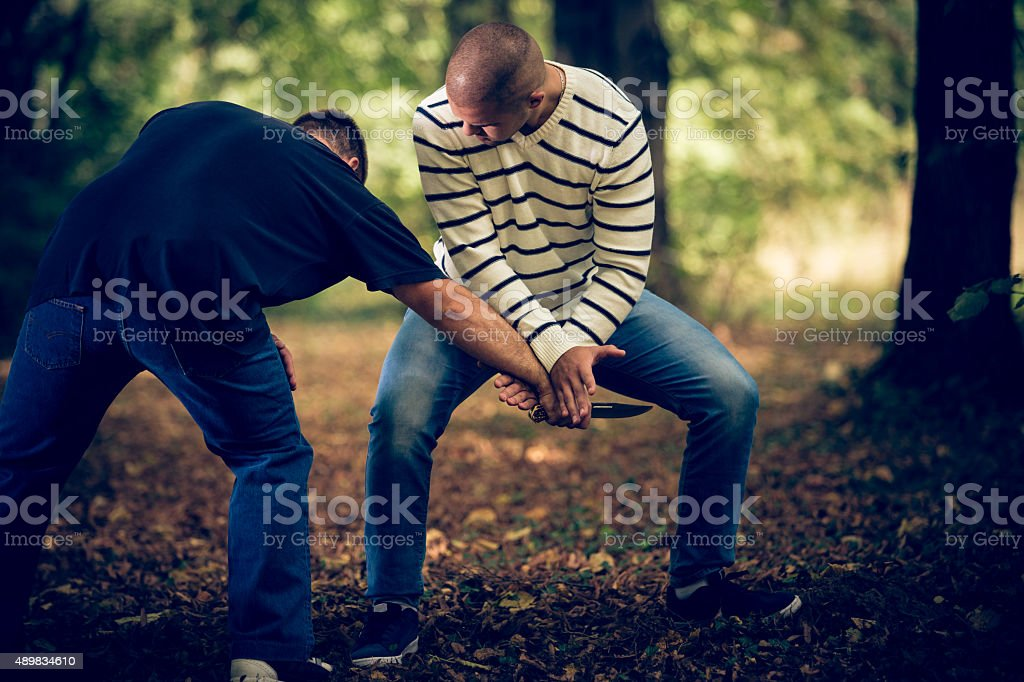 Self-defending against a knife-attacker stock photo