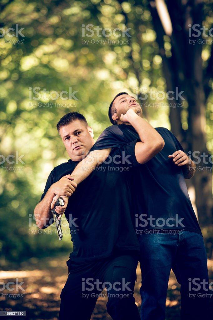 Self-defending from attacker with handgun stock photo