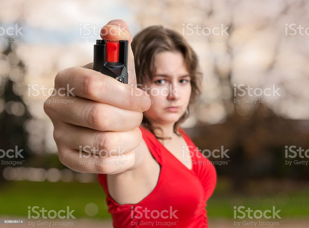 Self-defense concept. Young woman holds pepper spray in hand. stock photo