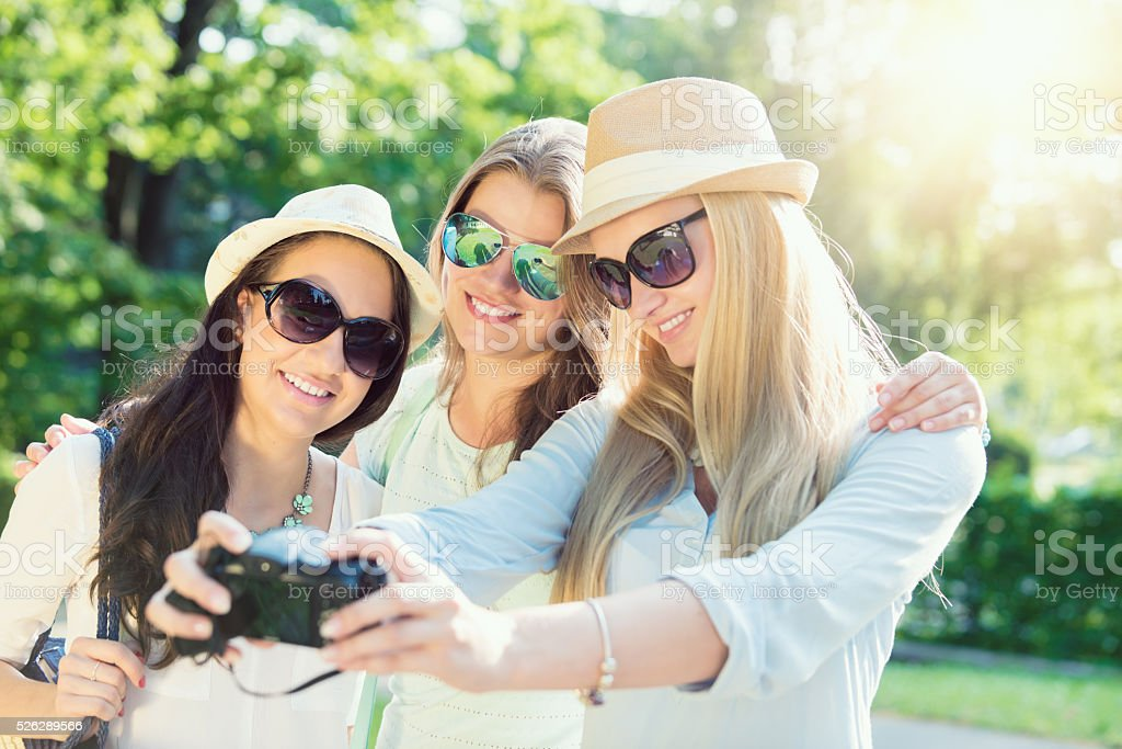Selfie. Friends taking picture at summer holidays, girls with camera stock photo