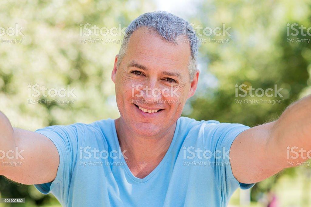 Selfie fun. Smiling mature man making selfie and grimacing stock photo