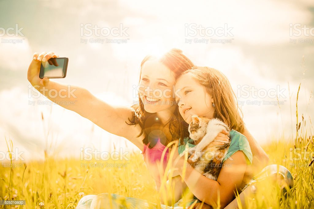 Selfie - mother, child and kitten stock photo