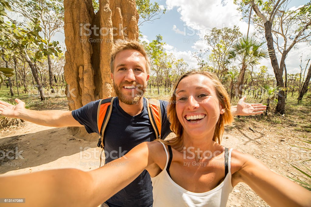 Selfie of caucasian couple with enormous termite mound, Australia stock photo