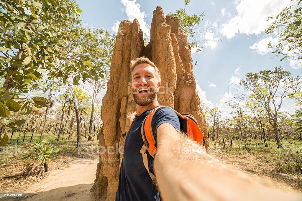 Selfie of caucasian male with enormous termite mound, Australia stock photo