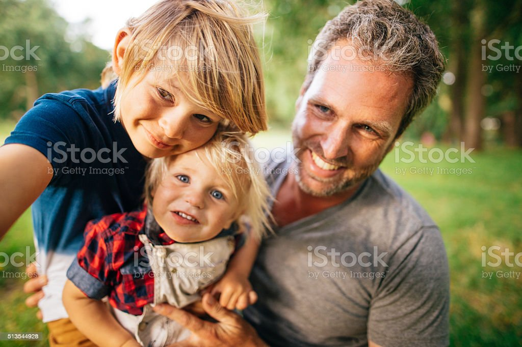 Selfie of father and his two sons in the park stock photo