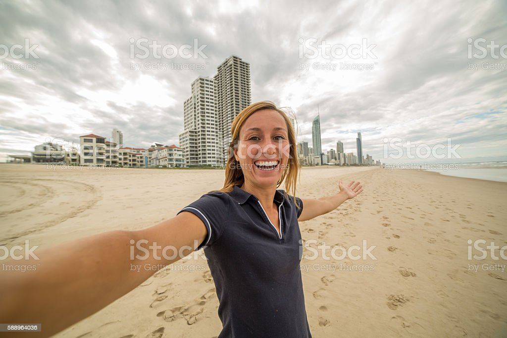 Selfie of girl on beach with city skyline on background stock photo