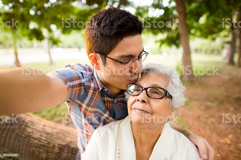 Selfie of grandson kissing grandmother on forehead stock photo