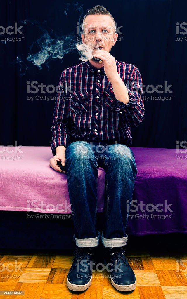 selfie of man sitting on bed and vaping e cigarette stock photo