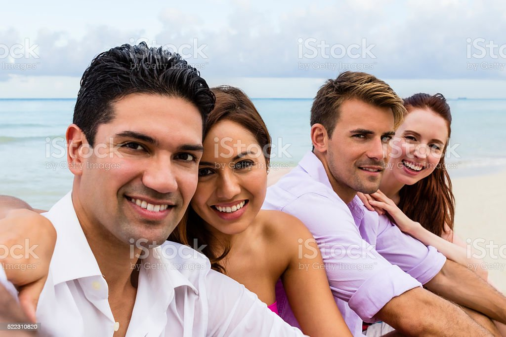 Selfie of two couples smiling and sitting on a beach stock photo