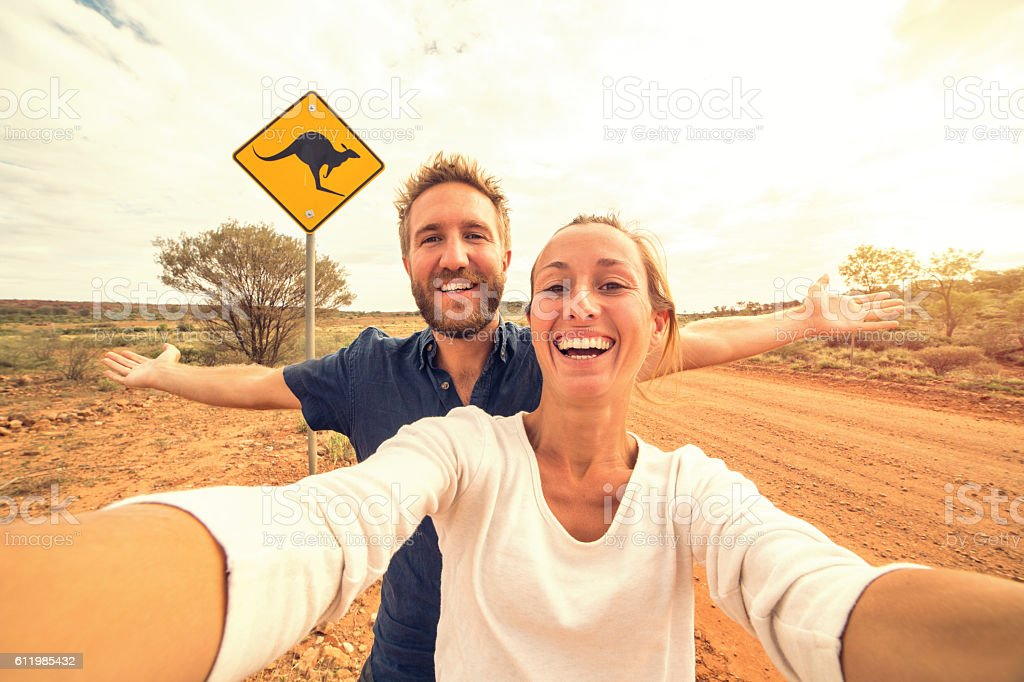 Selfie of young couple in Australia standing near kangaroo sign stock photo