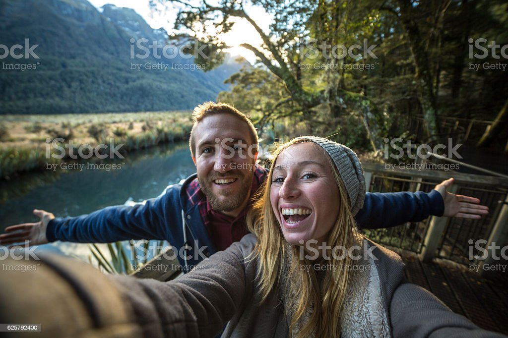Selfie of young couple in lake mountain landscape stock photo