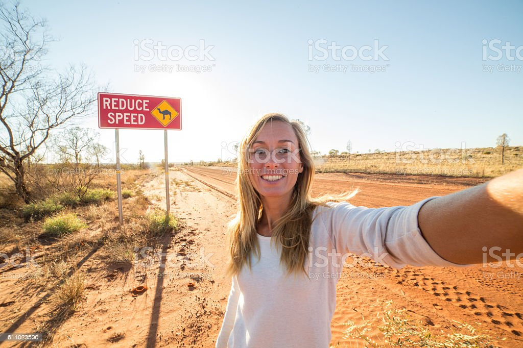 Selfie of young woman standing by Camel warning sign stock photo
