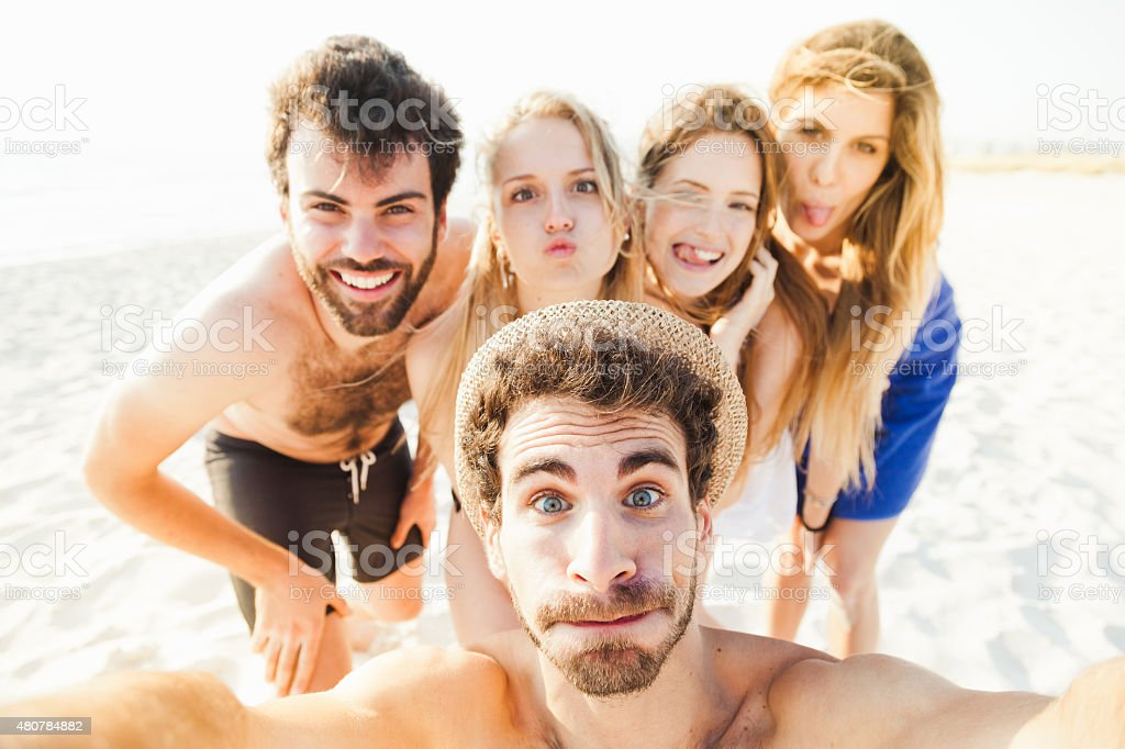 Selfie on the beach Five friends take photo together sea stock photo