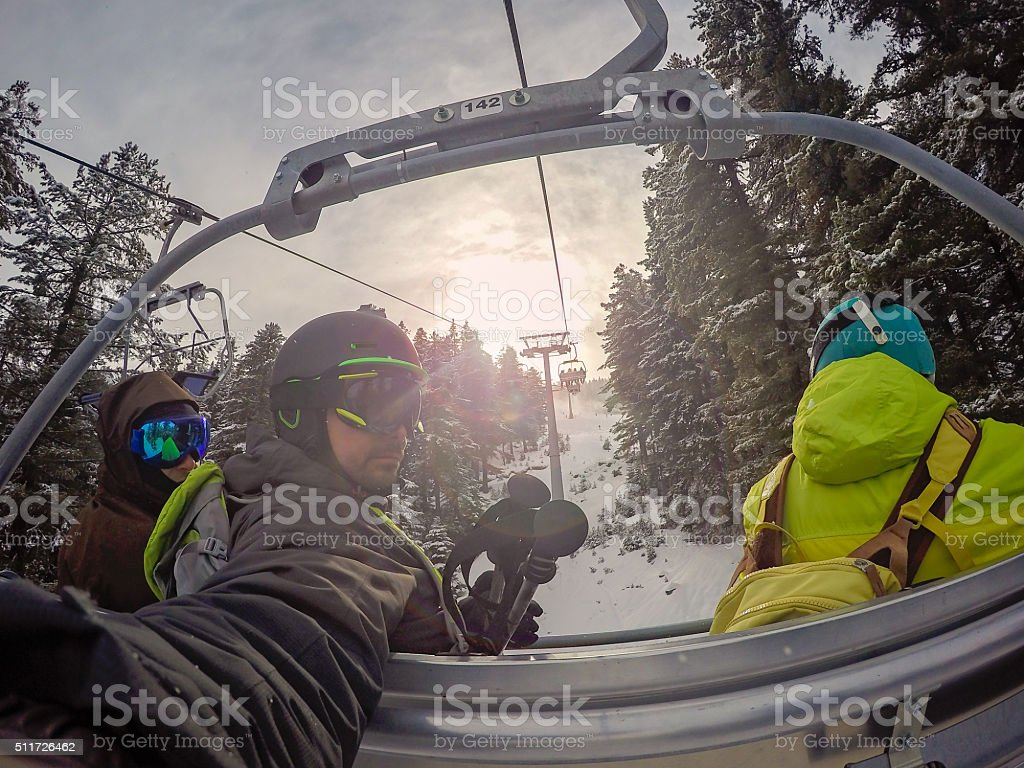 selfie on the chairlift among trees stock photo