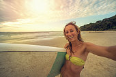 Selfie portrait of a caucasian female surfer carrying surfboard