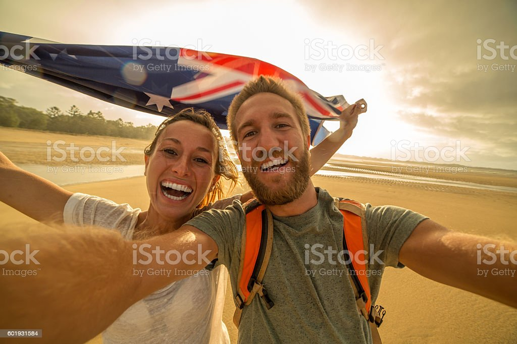 Selfie portrait of two young adults on beach holding flag stock photo