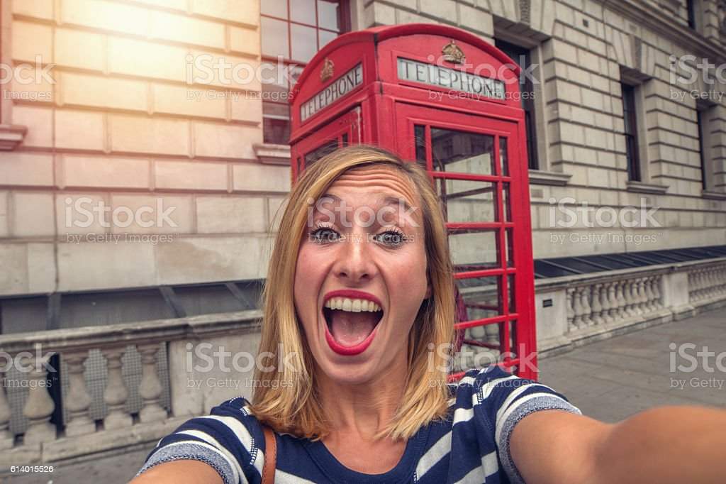 Selfie portrait of woman in London with classic phone box stock photo