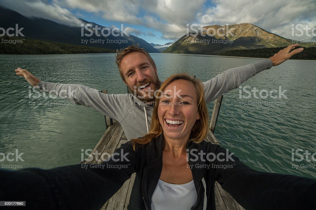 Selfie portrait on lake pier, couple having fun stock photo