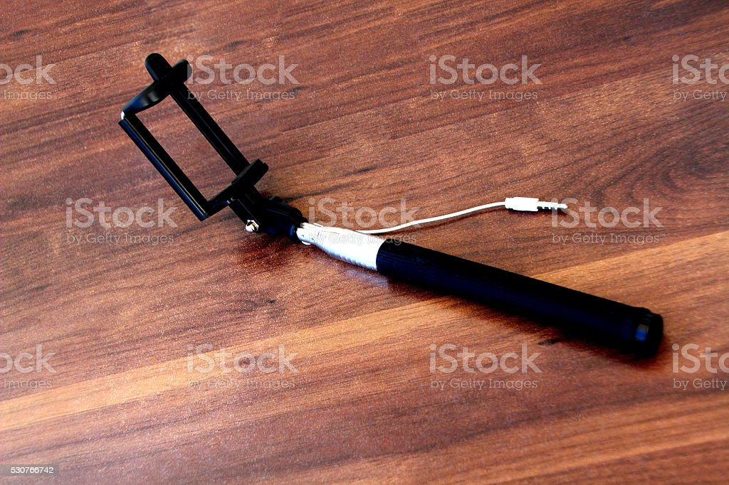 selfie stick on a wood table stock photo