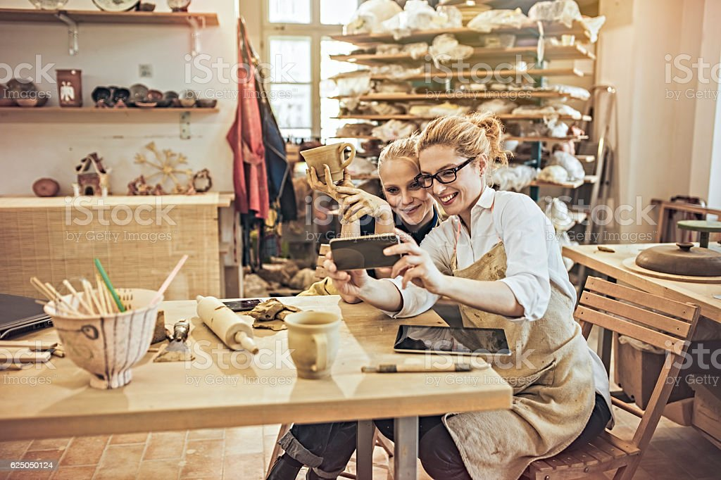 selfie with colleague in craft workshop stock photo