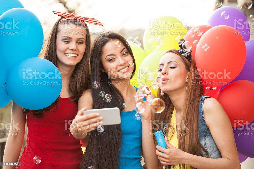 Selfie with friends blowing bubbles stock photo