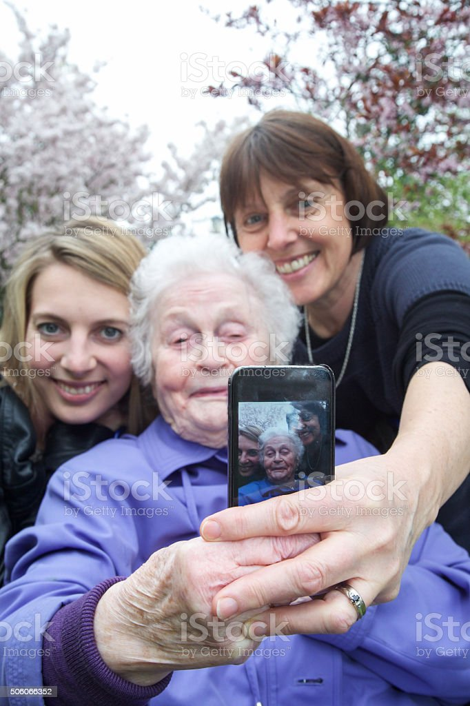 Selfies - three generations attempt to take a selfie! stock photo