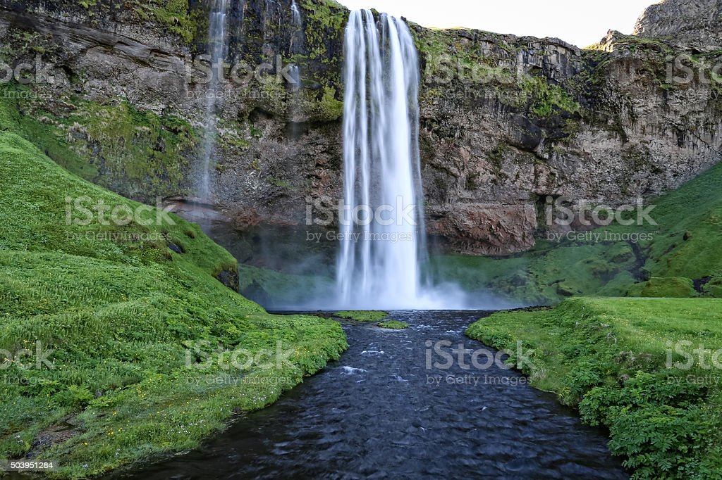 Seljalandsfoss waterfall pours its crystal clear water to the creek stock photo