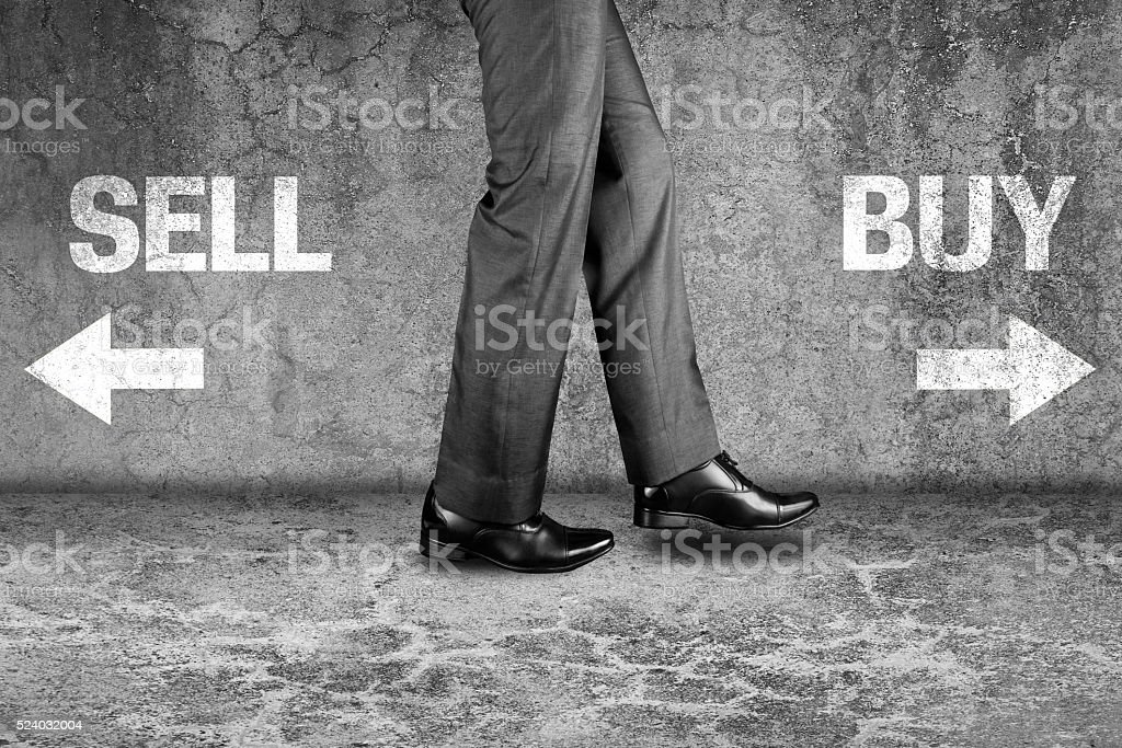 Sell or Buy written text on dirty wall stock photo